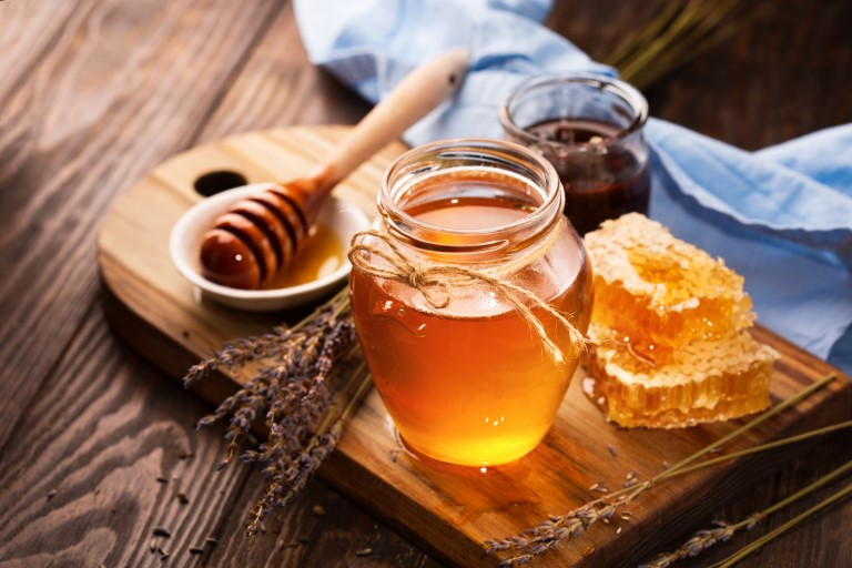 жидкий мед с сотами на деревянном подносе