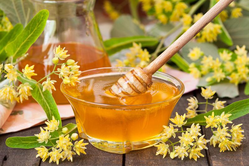 липовый мед в стеклянной тарелочке и с деревянным веретеном