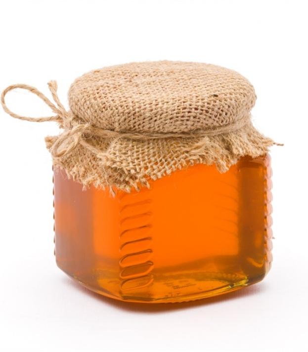 свежий прозрачный мед в стеклянной баночке