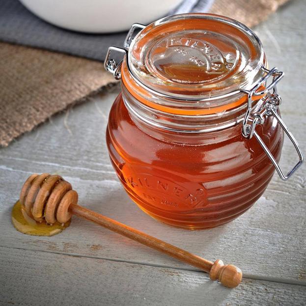 мед в закрытой баночке с деревянной ложечкой рядом