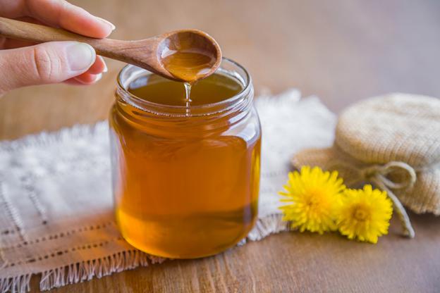 жидки мед стекает с деревянной ложечки