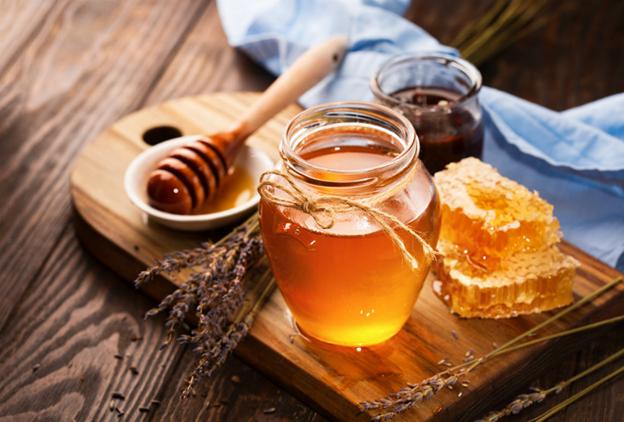 свежий жидкий мед на подносе с сотами, тарелочкой и лавандой