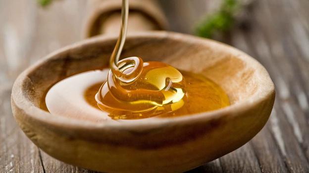 цветочный мед в деревянной чашке